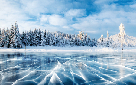 Foto de Blue ice and cracks on the surface of the ice. Frozen lake under a blue sky in the winter. The hills of pines. Winter. Carpathian, Ukraine, Europe - Imagen libre de derechos