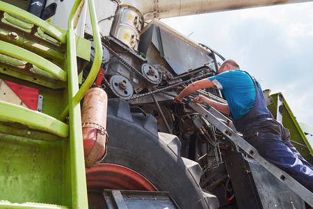 Photo for Combine machine service, mechanic repairing motor outdoors - Royalty Free Image