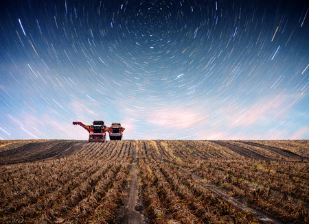 Photo pour Tractor plowing farm field in preparation for spring planting. Fantastic starry sky and the milky way - image libre de droit