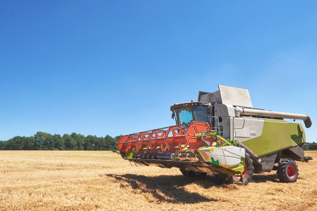 Foto per combine harvester working on a wheat field - Immagine Royalty Free