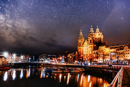 Photo pour Beautiful night in Amsterdam. Night illumination of buildings and boats near the water in the canal. - image libre de droit