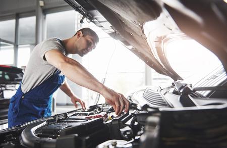 Photo pour Picture showing muscular car service worker repairing vehicle. - image libre de droit