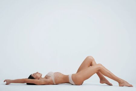 Foto de Having a good rest. Laying down on the white surface in the photo studio. - Imagen libre de derechos