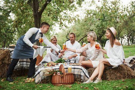 Foto de Even waiter have a good time during the service with these beautiful group of friends. - Imagen libre de derechos