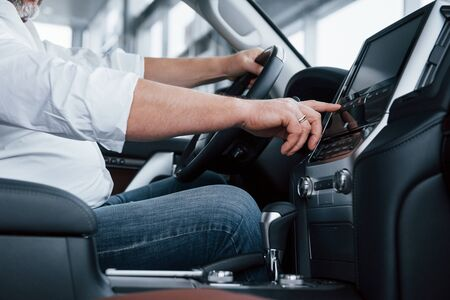 Photo pour Side close up view. Businessman in official clothes sits in a luxury car and pushing the buttons on the music player. - image libre de droit