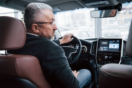 Photo pour Ready to the ride. View from behind of senior businessman in official clothes driving a modern new car. - image libre de droit