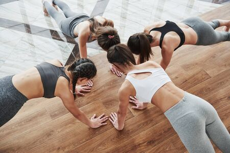 Photo for Young girls doing push ups together. Head near head pose on the wooden and tile floor. - Royalty Free Image