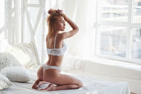 Foto de Touching hair by the hands. Hot redhead girl in underwear sits on the white bed before the windows. - Imagen libre de derechos