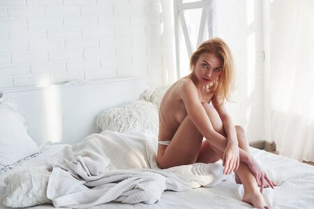 Foto de Full lenth view. Almost naked redhead girl covering her chest with legs and hands while sitting on the bed. - Imagen libre de derechos