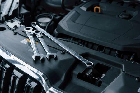 Foto de Black colored interior. Repair tools lying down on the engine of automobile under the hood. - Imagen libre de derechos