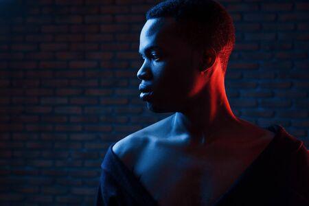 Photo pour Confident guy. Futuristic neon lighting. Young african american man in the studio. - image libre de droit
