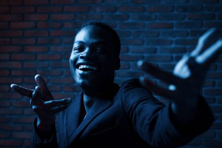 Photo pour Dark room. Cheerful guy. Young african american man in the studio. - image libre de droit