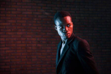 Photo pour Futuristic neon lighting. Young african american man in the studio. - image libre de droit