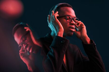 Photo for Enjoying listening music in headphones. In glasses. Futuristic neon lighting. Young african american man in the studio. - Royalty Free Image