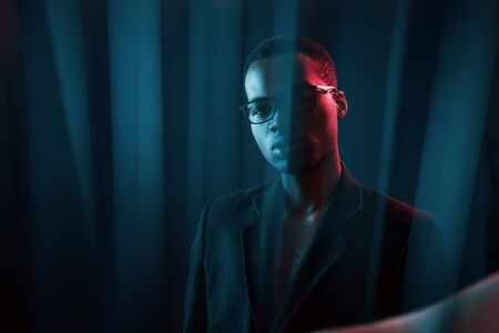 Photo for Interesting beams. Futuristic neon lighting. Young african american man in the studio. - Royalty Free Image