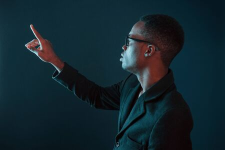 Photo pour Hands in front. Futuristic neon lighting. Young african american man in the studio. - image libre de droit