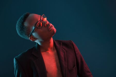 Photo for Fashion model. Futuristic neon lighting. Young african american man in the studio. - Royalty Free Image