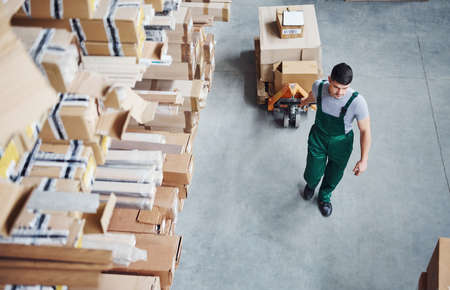 Photo for Top view of male worker in warehouse with pallet truck. - Royalty Free Image