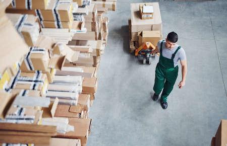Foto de Top view of male worker in warehouse with pallet truck. - Imagen libre de derechos