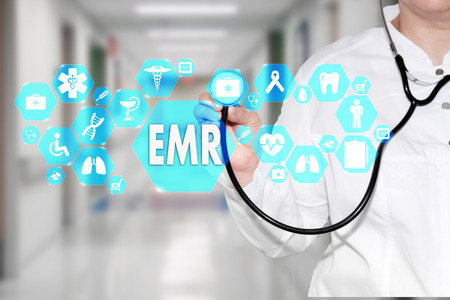 Foto de Electronic medical records. EMR on the touch screen with medicine icons on the background blur Doctor in hospital. - Imagen libre de derechos