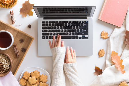 Foto de Workspace with red and yellow maple leaves, laptop, cup of tea, sweet homemade cookies. Top view of cozy office desk. Autumn background, flat lay. - Imagen libre de derechos
