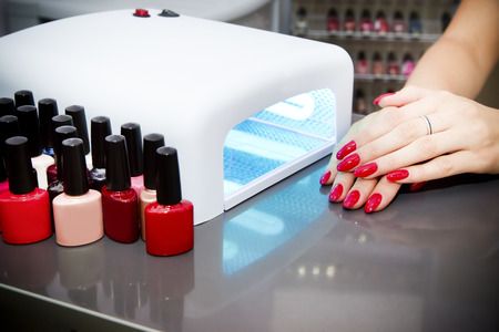 Foto de Manicure set in a beauty salon. Beautiful female hands. - Imagen libre de derechos