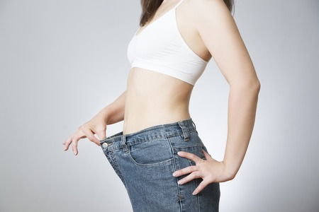 The concept of weight loss. Beautiful slender female body. Young woman in jeans large size.