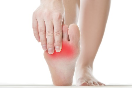 Foto de Pain in the foot. Massage of female feet. Pedicures. Isolated on white background. - Imagen libre de derechos