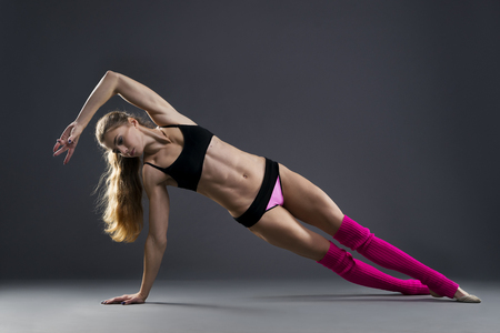 Photo pour Beautiful muscular woman doing exercise side plank on a gray background in studio - image libre de droit