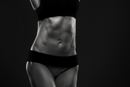 Photo for Attractive fitness woman in studio. Muscular abdomen close-up. Trained female body. Black and white photography - Royalty Free Image