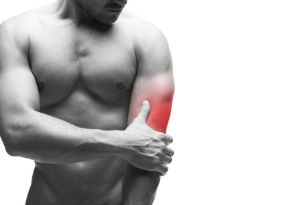 Foto de Pain in the elbow. Muscular male body with copy space. Isolated on white background with red dot. Black and white photography - Imagen libre de derechos