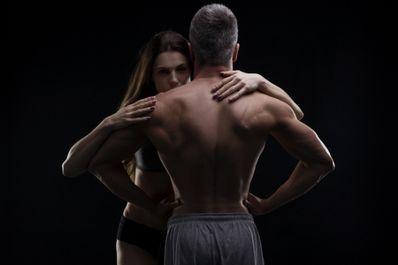 Photo for Young adult muscular man and woman. Sexy couple on black background - Royalty Free Image