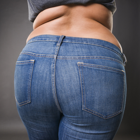 Photo pour Woman with fat buttocks in blue jeans, overweight female body closeup, gray studio background - image libre de droit