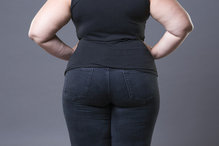 Photo for Fat female buttocks in blue jeans, overweight woman body closeup, gray studio background - Royalty Free Image
