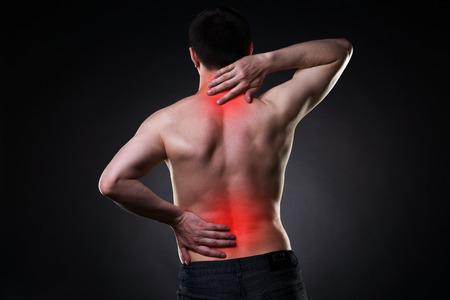 Photo pour Back pain, man with backache on black background with red dots - image libre de droit