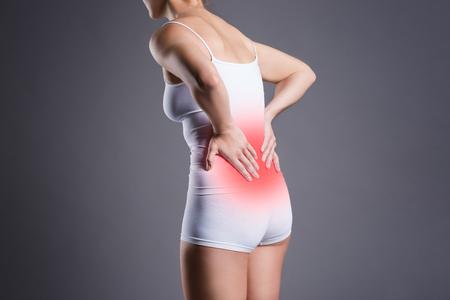 Foto de Back pain, kidney inflammation, ache in woman's body on gray background - Imagen libre de derechos
