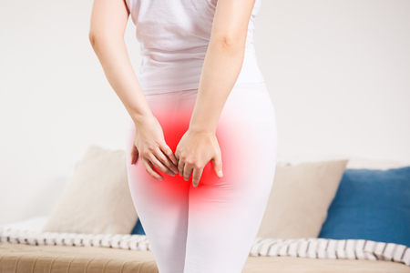 Photo pour Woman suffering from hemorrhoids at home, anal pain, painful area highlighted in red - image libre de droit