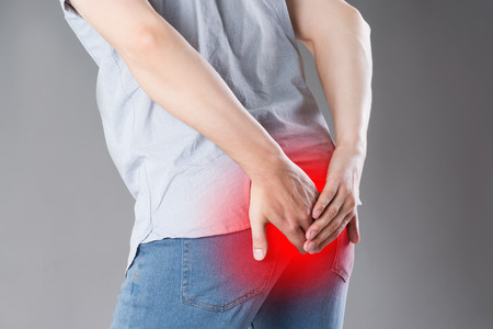 Photo pour Man suffering from hemorrhoids, anal pain on gray background, painful area highlighted in red - image libre de droit
