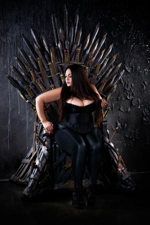 Photo pour Plus size fashion model sitting on the iron throne, sexy woman in gothic interior - image libre de droit