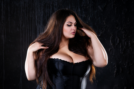 Foto per Sexy plus size model in black corset, fat woman with big natural breasts on dark background, body positive concept, studio shot - Immagine Royalty Free