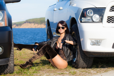 Photo for Sexy girl in a lingerie jacket and boots sitting between two cars on a background of water and sky - Royalty Free Image