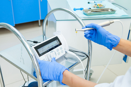 Foto de electronic device for the treatment of dental canals in the hands of a dentist in a treatment room. Photo without face - Imagen libre de derechos