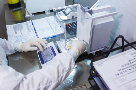 Foto de Pharmacist, a laboratory worker in sterile rubber gloves, weighs the manufactured tablets on the control scales. - Imagen libre de derechos