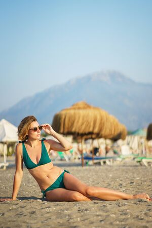 Photo for Portrait of a young beautiful girl with short hair at the beach. Stylish tanned slim girl in a swimsuit lies on a sandy beach. Young woman in a green bikini and sunglasses on the beach. - Royalty Free Image