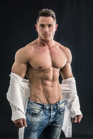 Photo pour Male bodybuilder opening his shirt revealing muscular torso, on black background - image libre de droit