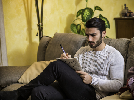 Photo for Young man sitting doing a crossword puzzle looking thoughtfully at a magazine, with his pencil to his mouth, as he tries to think of the answer to the clue - Royalty Free Image