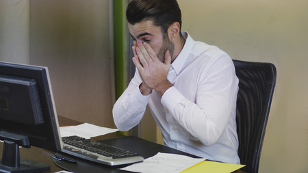 Photo for Tired bored young businessman sitting at his desk in front of his computer with his chin resting on his hand, sleepy - Royalty Free Image