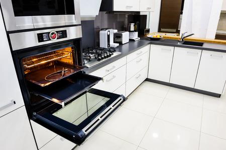 Photo pour Modern luxury hi-tek black and white kitchen, clean interior design, focu at oven with open door - image libre de droit
