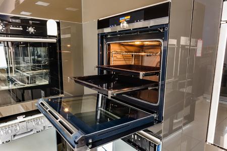 Photo pour Modern luxury hi-tek black and white kitchen, clean interior design, focus at oven with open door - image libre de droit