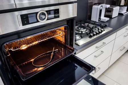 Photo pour Modern luxury hi-tek black and white kitchen, clean interior design, focu at oven with door open - image libre de droit